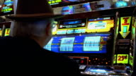 Medium shot man playing slot machine and hitting jackpot in Las Vegas casino