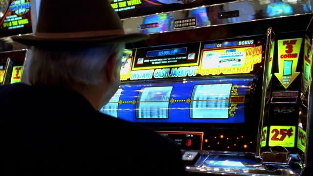 Medium shot man playing slot machine and hitting jackpot in Las Vegas casino
