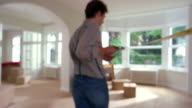 Medium shot man pulling tape measure across living room to arch w/boxes, chair and painting in background near windows