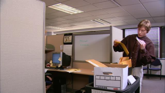 Medium shot man pushing mail cart / delivering envelopes to people in cubicles