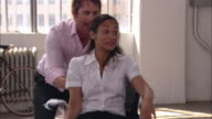 Medium shot man pushing woman in office chair in empty loft/ pan man picking up bubble wrap off floor and laughing/ Brooklyn, New York