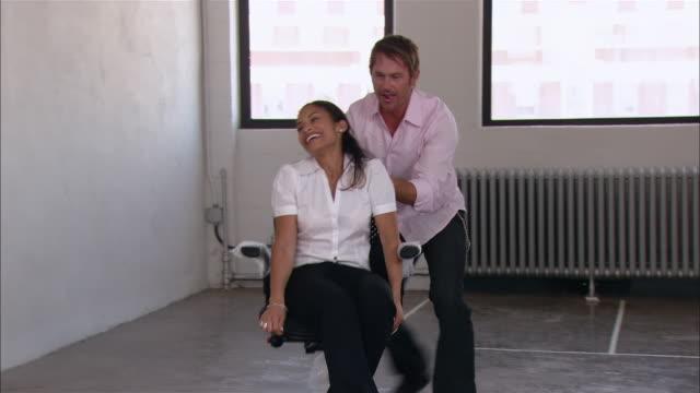 Medium shot man pushing woman in office chair in empty loft space/ Brooklyn, New York
