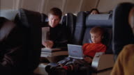 Medium shot man reading newspaper on airplane / young boy looking at portable DVD player and showing man screen