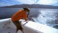 Medium shot man relaxing in fighting chair on boat as his fishing line gets a bite/ man grabbing rod, bracing himself in chair and reeling it in/ California