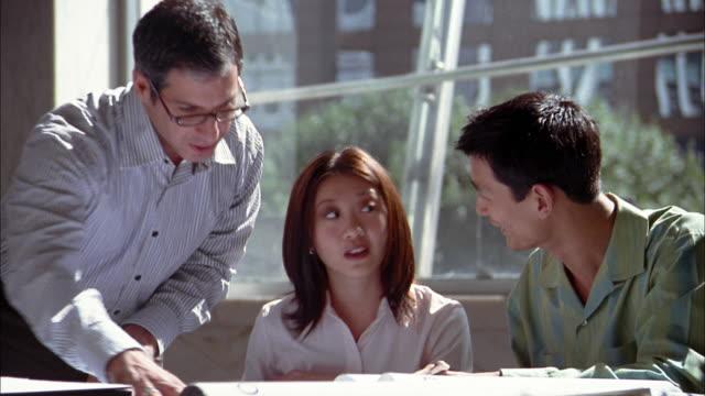 Medium shot man reviewing construction blue prints w/Asian man and woman