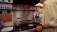 Medium shot man salting scrambled eggs cooking in pan on stove
