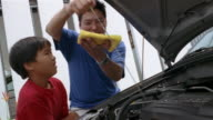Medium shot man showing boy how to check oil under the hood of car / wiping off dipstick