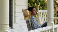 Medium shot man sitting in rocking chair on porch and waving