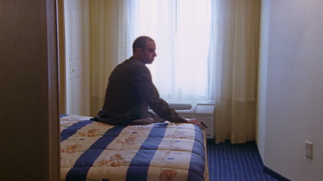 Medium shot man sitting on bed in hotel room / looking out window