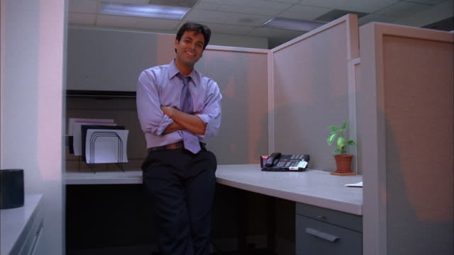 Medium shot man smiling at CAM w/arms folded by office cubicle
