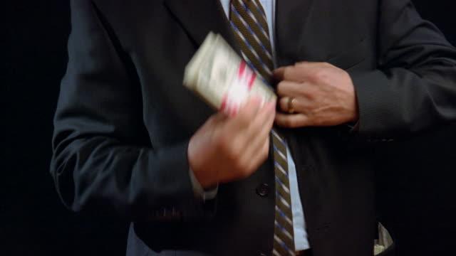 Medium shot man stashing bundles of money in his suit jacket before buttoning up