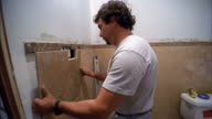 Medium shot man tiling bathroom wall