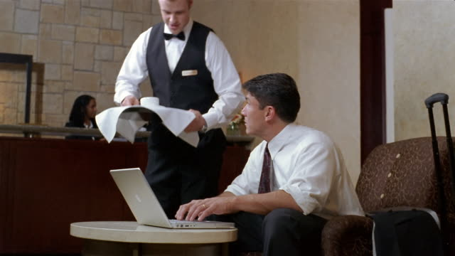 Medium shot man using laptop computer in hotel lobby / waiter bringing him cup of coffee