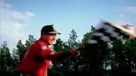 Medium shot man waving checkered flag at race track / Alabama