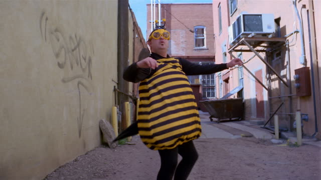 Medium shot man wearing bee costume dancing in alley