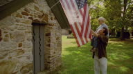 Medium shot man with boy on shoulder pointing to US flag on stone building/ Solebury, Pennsylvania