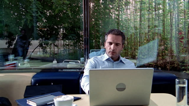 Medium shot man working at laptop computer in cafe / man walking by outside window / Berlin