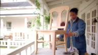 Medium shot mature Black woman examining and  varnishing a wooden chair w/brush on balcony