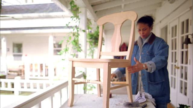 Medium shot mature Black woman examining and  varnishing a wooden chair w/brush on balcony