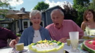 Medium shot mature couple blowing out candles on cake and clapping