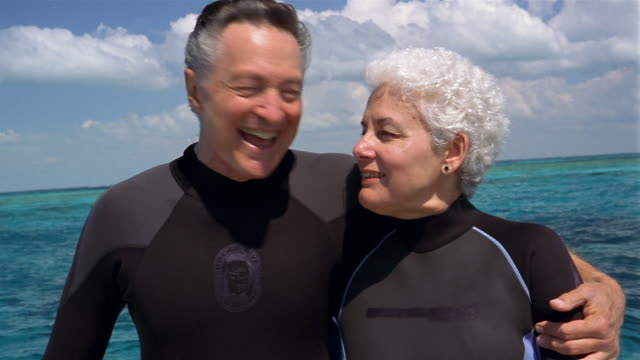 Medium shot mature couple wearing wet suits kissing on boat with blue water in background