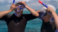 Medium shot mature couple wearing wet suits putting on snorkeling gear