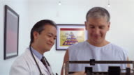 Medium shot Mature doctor weighing patient on scale and frowning/ Panama City, Panama