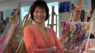 Medium shot Mature woman artist standing near paintings in art studio