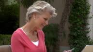 Medium shot Mature woman talking on cell phone on patio/ San Antonio, Texas, USA