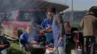 Medium shot men at tailgate party laughing as they refuse burnt hot dogs and hamburgers from grill/ Connecticut