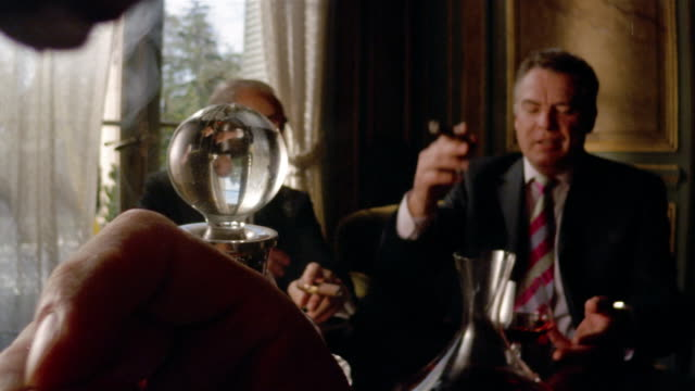 Medium shot men smoking cigars and talking / dolly shot reflection in stopper of decanter / man lighting cigar in foreground