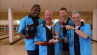 Medium shot men's bowling team in blue jerseys holding trophy / smiling and gesturing at CAM