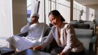 Medium shot Middle Eastern man and Asian woman talking at informal business meeting / woman gives man documents