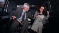 Medium shot middle-aged businessman looking at binder and young businesswoman looking at pda /man putting  his hand on woman's knee in limo / woman removing his hand