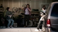 Medium shot middle-aged women performing in garage rock band / teenage girls dancing / forcing teenage boy by the arm to join them