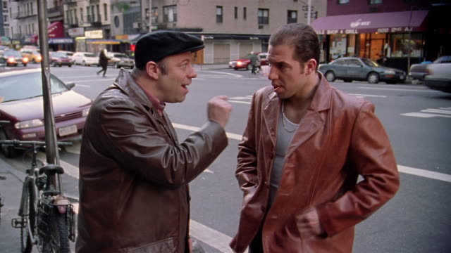 Medium shot mobster talking animatedly and gesturing to another mobster on street