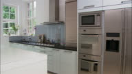 Medium shot modern kitchen cabinet and oven/ pan kitchen island and dining area/ London