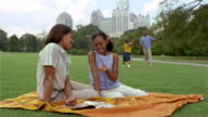 Medium shot mom and daughter reading magazine on blanket in Piedmont Park / dad + son playing catch in background