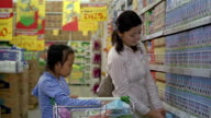 Medium shot mom and daughter shopping in aisle at supermarket/ picking up box of Ultra Milk + putting in cart