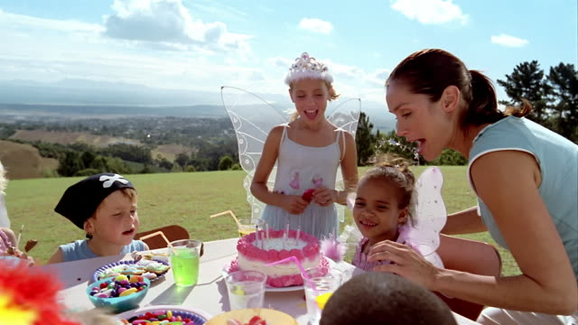 Medium shot mother bringing birthday cake to children in costumes at birthday party / South Africa