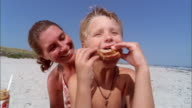 Medium shot mother embracing young son eating peanut butter and jelly sandwich on beach