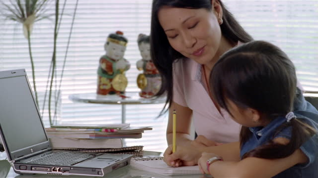 Medium shot mother helping daughter with her homework / smiling and hugging her