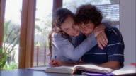 Medium shot mother helping son w/homework and hugging him