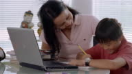 Medium shot mother helping son with homework / smiling and hugging her / answering cell phone