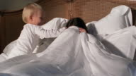 Medium shot mother hiding from child under sheet in bed / reavealing face to child