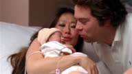 Medium shot mother holding newborn baby on her belly on hospital bed / father kissing baby / Brussels