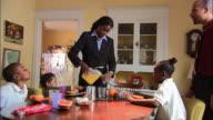 Medium shot mother pouring orange juice and three children sitting around breakfast table