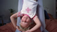 Medium shot mother swinging daughter upside down on bed / father lying and son jumping on bed / South Africa