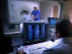 Medium shot MRI tech working monitor in foreground and woman exiting MRI machine with assistance of male in background