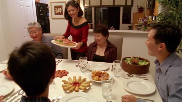 Medium shot multigenerational family sitting around dining table for dinner / passing around food / Honolulu